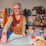 Charlane in her sewing room wearing a red and orange top measuring fabric